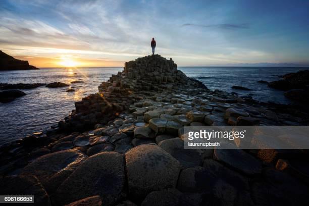 Woman standing on Giants Causeway at sunset, County antrim, Northern Ireland, UK