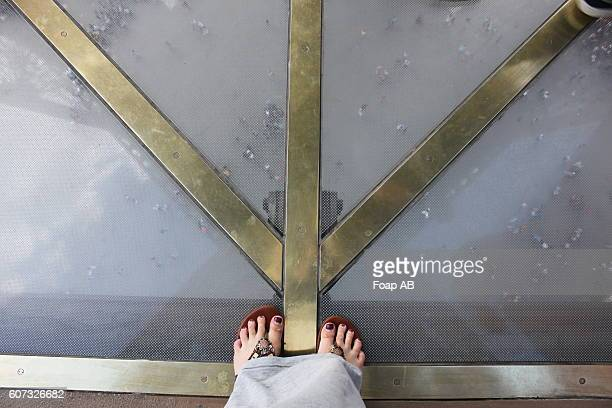 Woman standing on glass floor