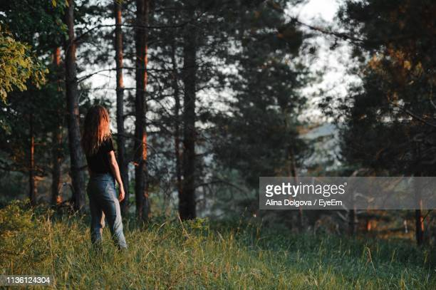 Woman Standing On Grass In Forest