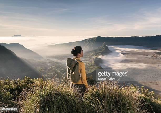 woman standing on hillside near mount bromo
