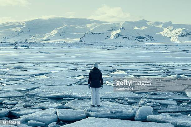 Woman standing on ice floe on frozen lake, Iceland