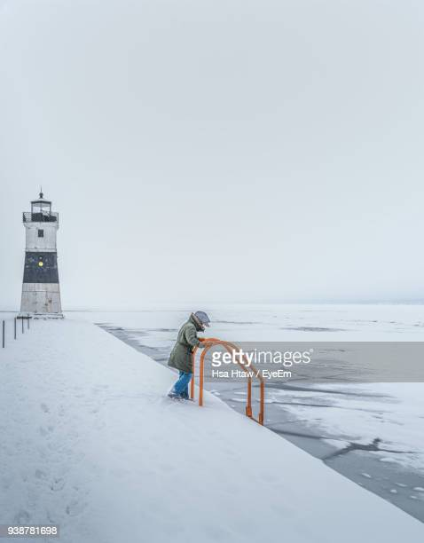 Woman Standing On Jetty By Lighthouse Against Sky During Winter