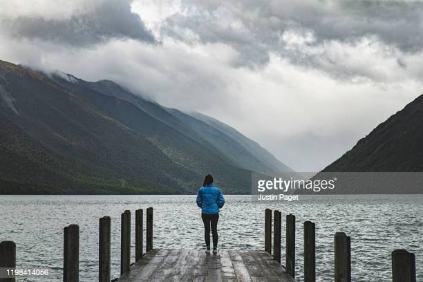 woman standing on jetty looking over lake - moody sky stock pictures, royalty-free photos & images
