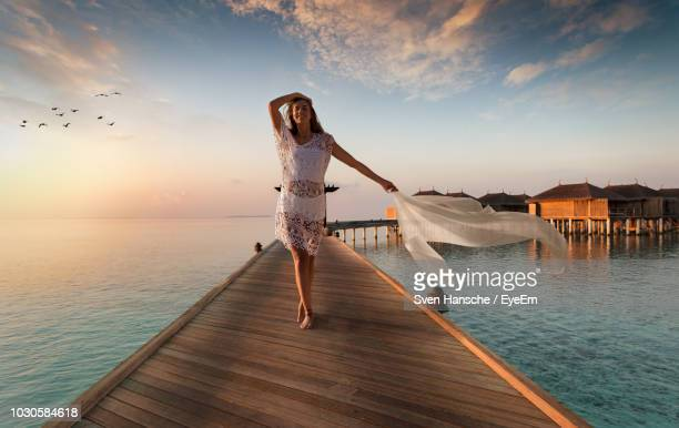 woman standing on jetty over sea against sky during sunset - jetty stock pictures, royalty-free photos & images