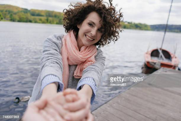 Woman standing on jetty, pulling on mans hand