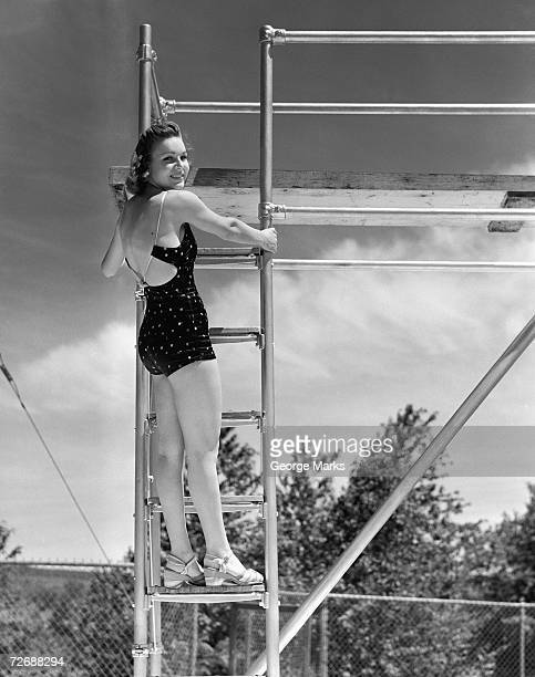 Woman standing on ladder at springboard, (B&W)