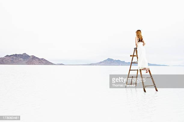 Woman standing on ladder in lake looking out