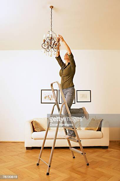 woman standing on ladder trying to change light bulb in chandelier