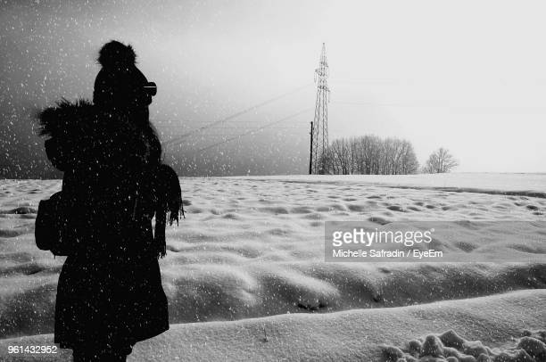 Woman Standing On Landscape During Winter Against Sky