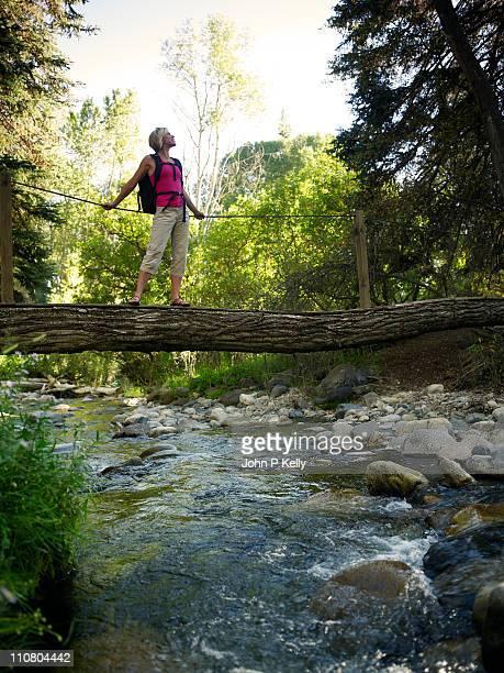 Woman standing on log bridge over creek