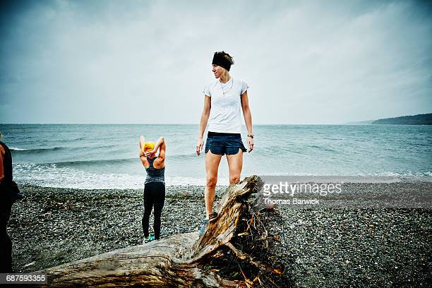 Woman standing on log on beach after run
