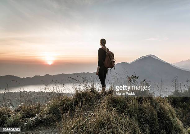 woman standing on mount batur at sunrise - rucksacktourist stock-fotos und bilder