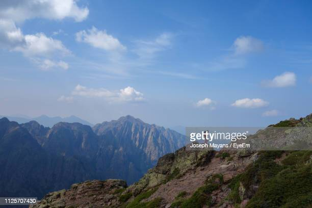 woman standing on mountain against blue sky - corsica stock-fotos und bilder