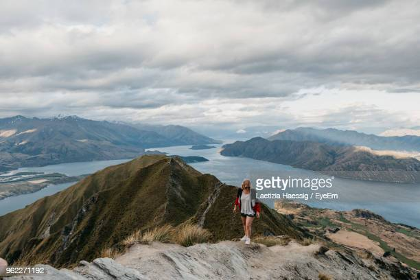 Woman Standing On Mountain Against Cloudy Sky