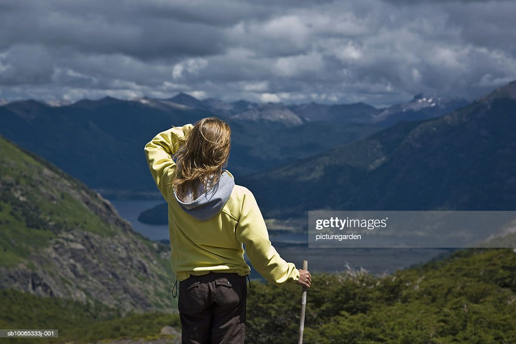 Woman standing on mountain, looking over valley, rear view : Foto stock
