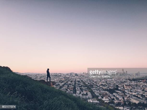 Woman Standing On Mountain Overlooking Cityscape Against Sky During Sunset