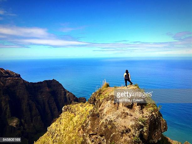 Woman Standing On Mountain Peak By Blue Sea Against Sky
