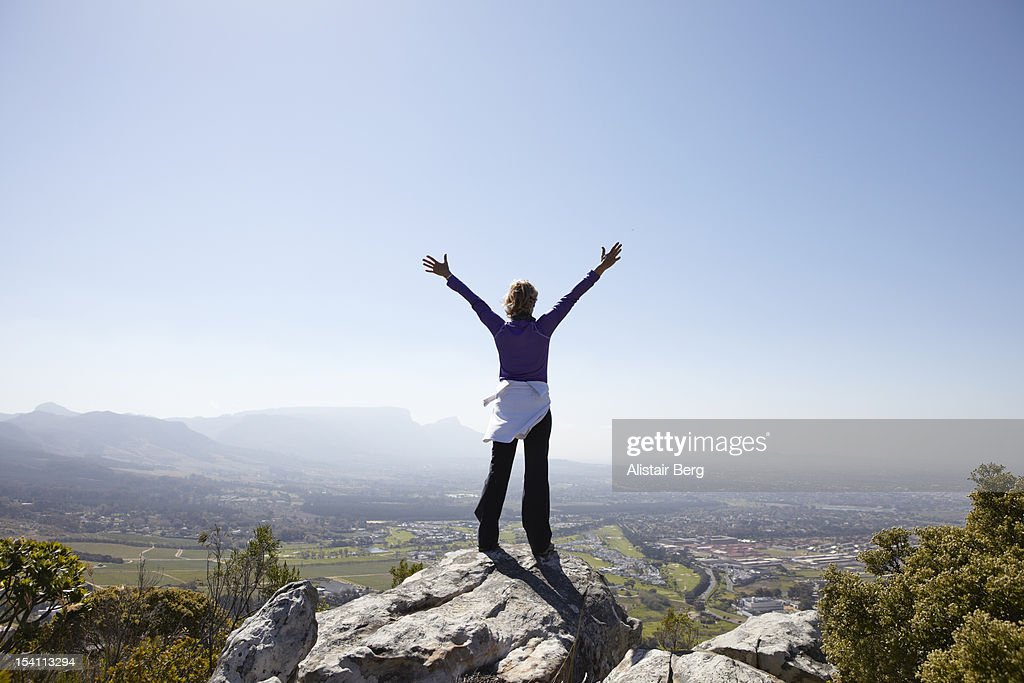 Woman standing on mountain with arms stretched out : Stockfoto