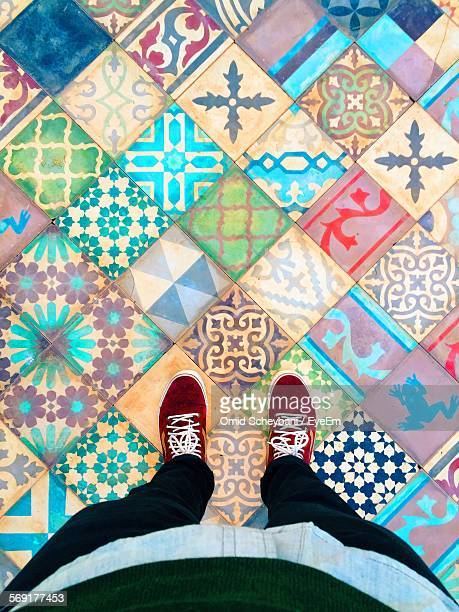 Woman standing on multi colored tiled floor