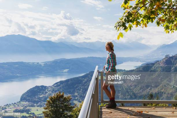 woman standing on observation point above millstatt lake, carinthia, austria - carinthia stock pictures, royalty-free photos & images