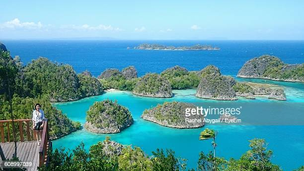 woman standing on observation point at raja ampat islands - raja ampat islands stock photos and pictures