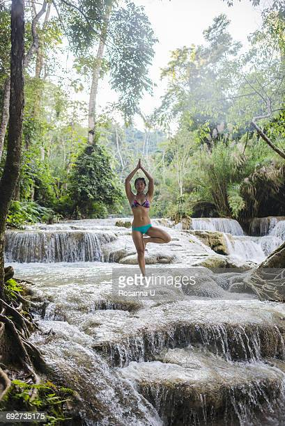 Woman standing on one leg, in tree pose, in Kuang Si waterfall, Luang Prabang, Laos