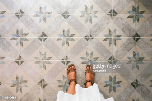 woman standing on ornate tiled floor - zuid europese etniciteit stockfoto's en -beelden