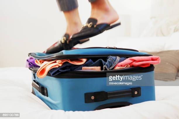 Woman standing on overfilled suitcase.