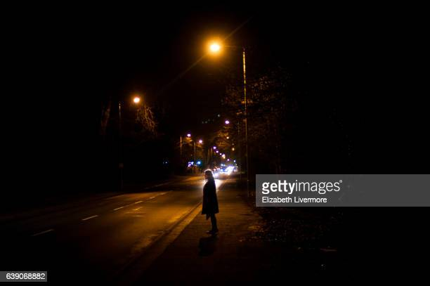 Woman standing on pavement at night