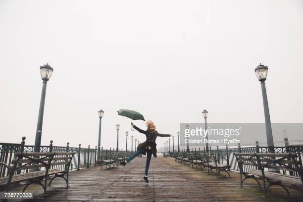Woman Standing On Pier Against Clear Sky