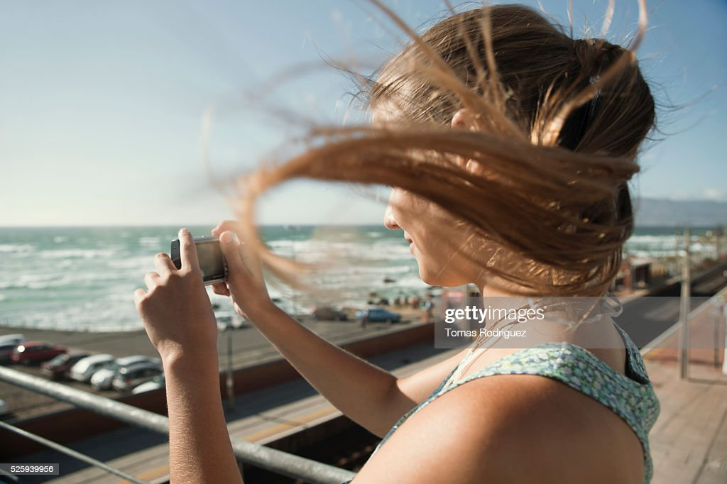Woman standing on pier and taking picture : Stockfoto