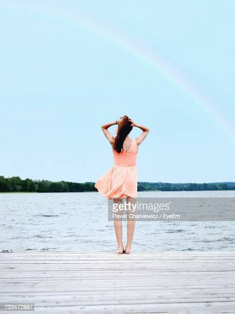 Woman Standing On Pier By Lake