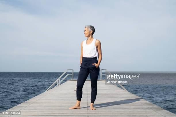 woman standing on pier - cheveux courts photos et images de collection