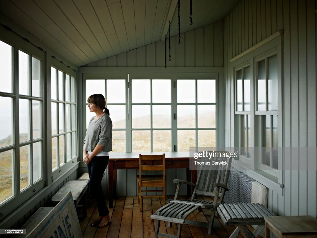Woman standing on porch of vacation home : Stockfoto
