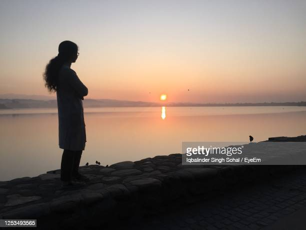 woman standing on promenade against sky during sunset - chandigarh stock pictures, royalty-free photos & images