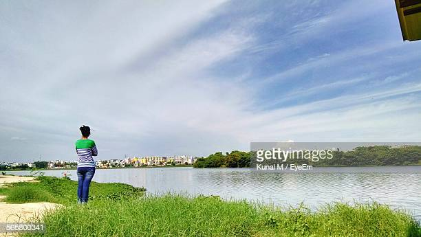Woman Standing On Riverbank