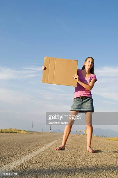 Woman standing on road with cardboard sign