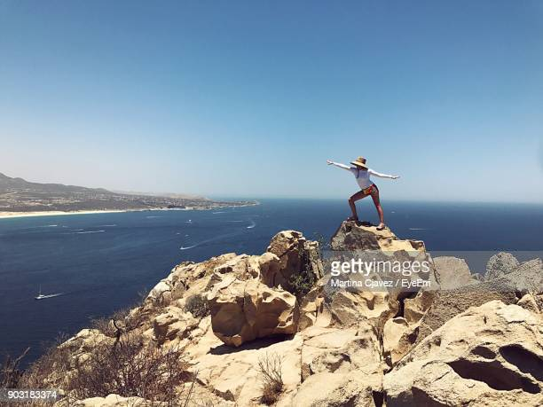 Woman Standing On Rock Against Blue Sky