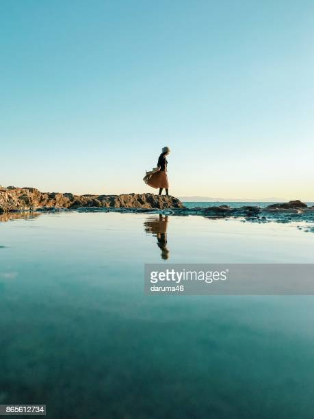 woman standing on rock beside sea - escapism stock photos and pictures