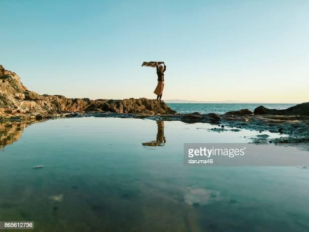海の横にある岩の上に立っている女性