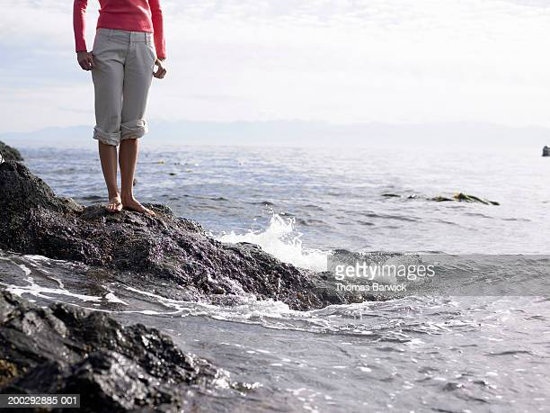 woman standing on rock beside shoreline, low section - rolled up pants stock pictures, royalty-free photos & images