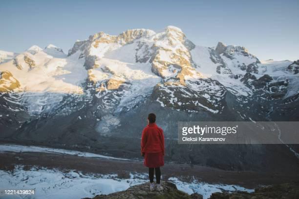 woman standing on rock by gorner glacier in valais, switzerland - 冠雪 ストックフォトと画像