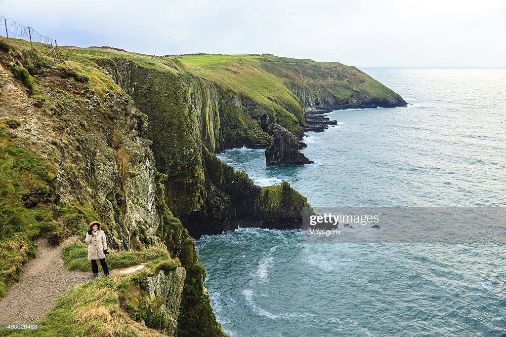 Woman standing on rock cliff by ocean Co. Cork Ireland : Stock Photo
