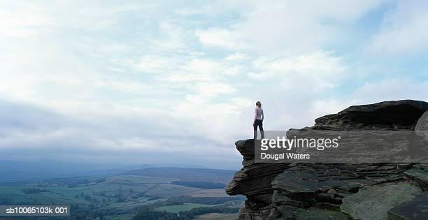 Woman standing on rock edge looking out across valley