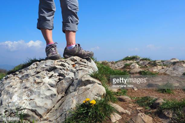 Woman standing on rock, feet and legs only