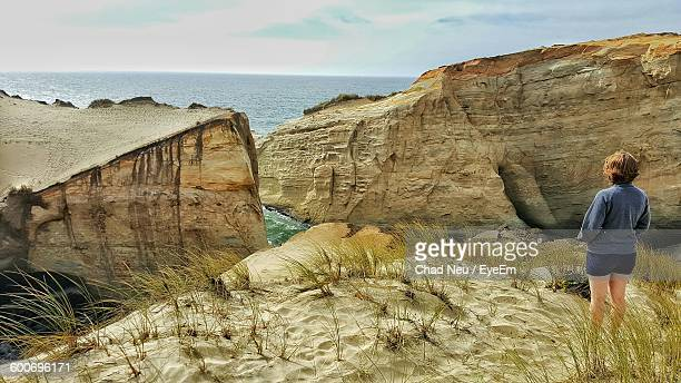 woman standing on rock formations at sea against sky - neu stock pictures, royalty-free photos & images