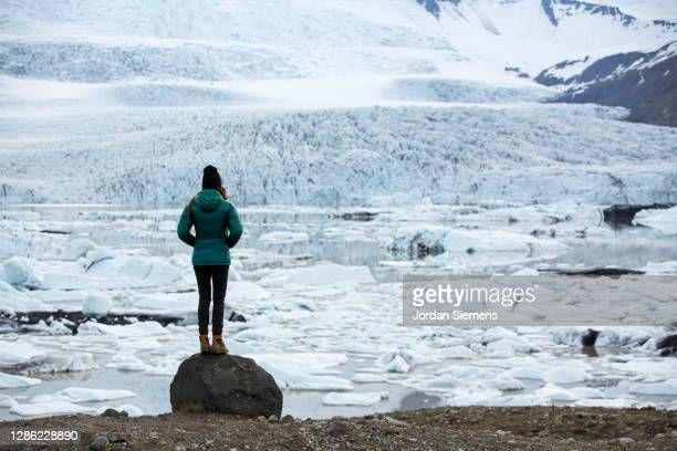 a woman standing on rock in front of a giant glacier in iceland. - coat stock pictures, royalty-free photos & images