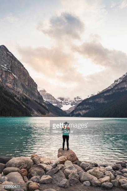 woman standing on rock, looking at lake view, rear view, lake louise, alberta, canada - banff stock photos and pictures