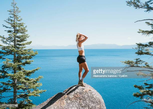 woman standing on rock over sea against sky - emerald bay lake tahoe stock pictures, royalty-free photos & images