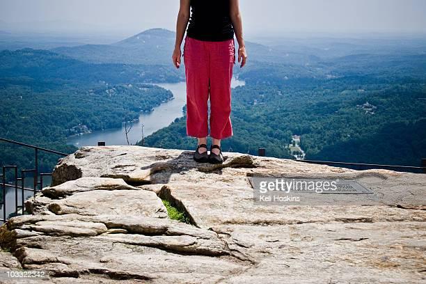 Woman standing on rock overlooking valley